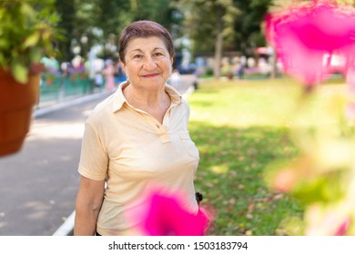 A woman in the Park walks on a Sunny summer day. The older woman with a good mood looking at the camera