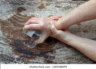 A woman with Parkinson's shakes her hands so badly that she can no longer hold a glass. Strongly trembling hands of an older woman