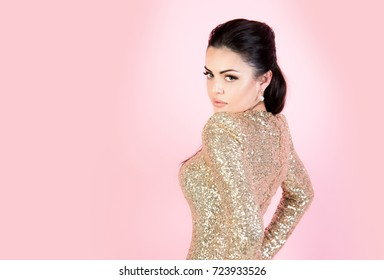 Woman in party dress with golden sequins. Girl with brunette hair on pink background. Fashion and style. Beauty and makeup. Holidays, birthday, new year, christmas, anniversary celebration, copy space