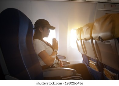 woman passenger of the aircraft on boarding in sick of airfly, worry and pray for the safty in take on/off, upset fearing on the fly