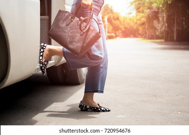 Woman passenger with black hand bag getting off  the bus in vacation