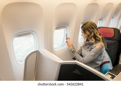 Woman passenger in business class of airplane. Taking photographs with her phone though the window..