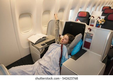 Woman passenger relaxing at the business class of airplane in comfortable single seat. Flight at first class plane