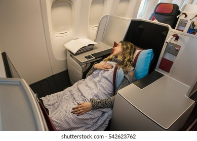 Woman passenger sleeping at the business class of airplane in comfortable single seat. Flight at first class plane