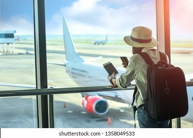 woman passenger or traveler tourist looking at next flight schedule on mobile, in worry of the flight schedule in late or delay, sitting upset in the transit hall of the airport waiting for aircraft