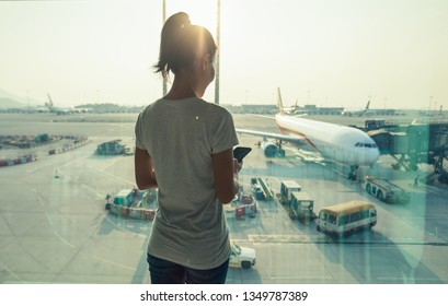 Woman passenger using mobile phone in airport