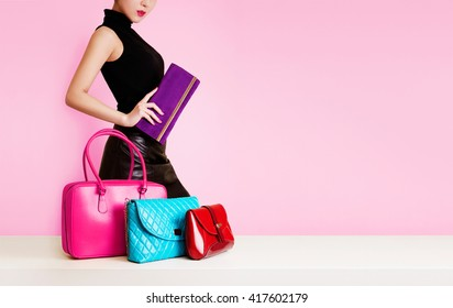 Woman passing in front of many bags and purses. shopping. fashion image. isolated on pink background.