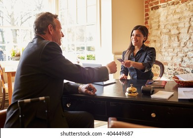 Woman passing room key to a guest at check-in desk of hotel