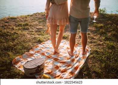 A woman in a pastel pink dress stands next to a man in in a denim shorts by the river on a a picnic. A loving romantic couple in a magical sunset