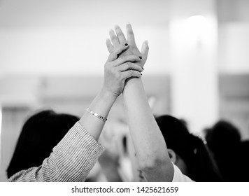 Woman Pastor pray for Worship team in church.Group of diverse hands holding each other and pray for support together.Worship teamwork and Unity in Church.Black and white tone.