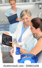 Woman patient at dental surgery dentist show teeth x-ray tablet