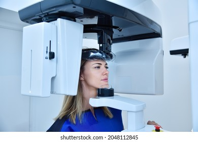 Woman patient make a panoramic computer tomograph in clinic. Dentistry and health care concept.