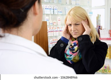 Woman as a patient in pharmacy needs medicine against migraine and headache