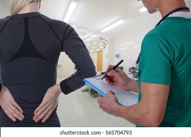Woman patient suffering from back pain during medical exam by doctor . Sports exercising injury.