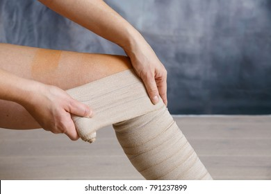 Woman patient with varicose veins applying elastic compression bandage after surgery. Curative treatment, thrombosis prevention and senior health care concept.