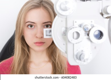 woman patient waiting for eye examination with phoropter at optometric clinic