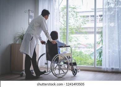 Woman patients sit on a wheelchair with doctor.