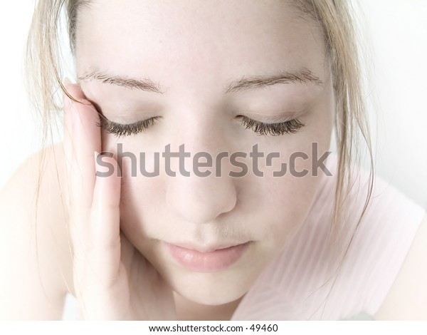 Woman patting water over her face, high key, pale pink tones.