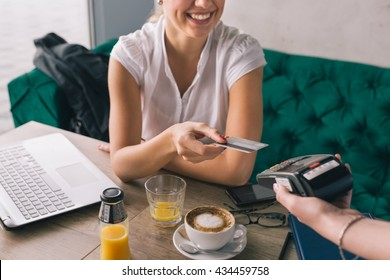 Woman pay with credit card in cafe bar