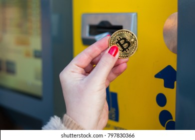 Woman pay with gold bitcoin at the vending machine