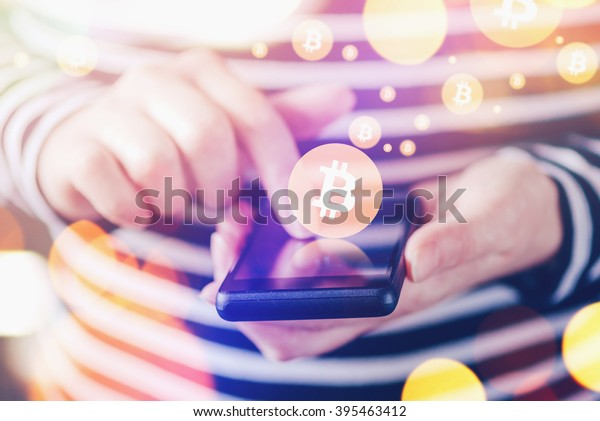 Woman paying with Bitcoins over smartphone, close up of female hands using mobile device to complete online transaction, nice bokeh, selective focus.