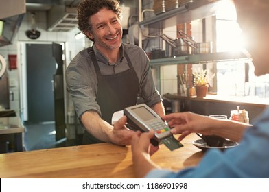 Woman paying by credit card and entering pin code on reader holded by smiling barista in cafeteria. Customer using credit card for payment. Mature cashier accepting payment over nfc technology.
