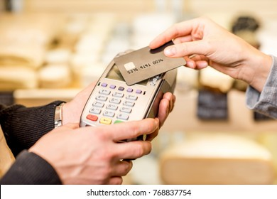 Woman paying with card contactless in the food store. Close-up view on the terminale and card