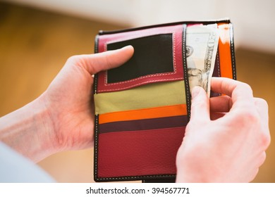 Woman paying in cash from a wallet, point of view angle. Shallow DOF.