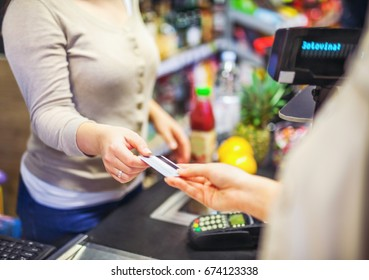 Woman paying with a credit card in a supermarket close up