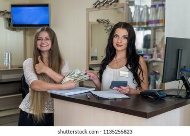 Woman paying dollars to administrator in beauty salon