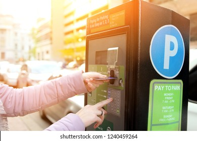 woman is paying his parking using credit card at  parking pay station terminal