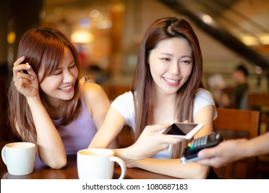Woman paying with mobile phone in cafe shop