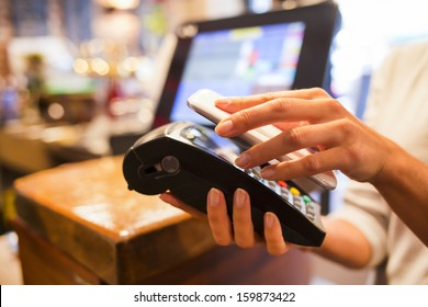 Woman paying with NFC technology on mobile phone, restaurant, cafe, bar