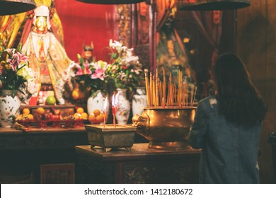 A woman paying respect to buddha image in Chinese temple