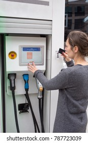 Woman pays with a card at a charging station for electric cars