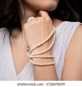 woman with pearl diamond necklace in hand