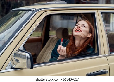 Woman peeking out of car window, woman with lipstick, woman in car
