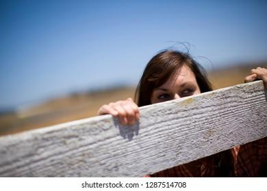 Woman peeking over fence on farm
