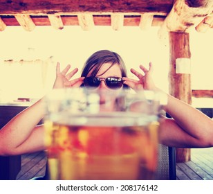 woman peeking over a fresh draft beer as her drink toned with a vintage retro style instagram filter