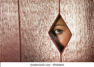 Woman peeks through a diamond shaped hole in a wall. Horizontal shot.