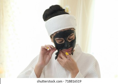 woman is peeling the mask on her face.