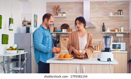 Woman peeling off oranges for nutritious smoothie in kitchen. Husband wearing denim shirt. Cheerful family making together organic healthy fresh nutritious tasty juice for breakfast from fresh fruits