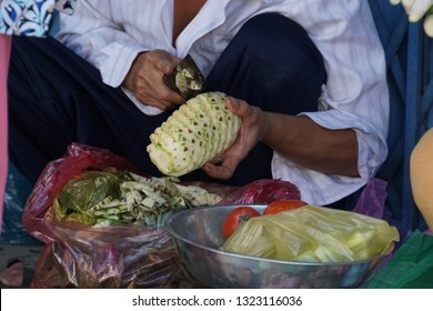 Woman peeling a pineapple with a cutter. Female seller on the market street of Saigon City, Vietnam.