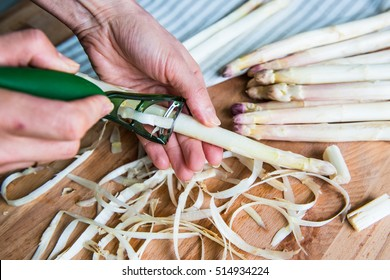 Woman peels asparagus. Wooden background with textil napkin.