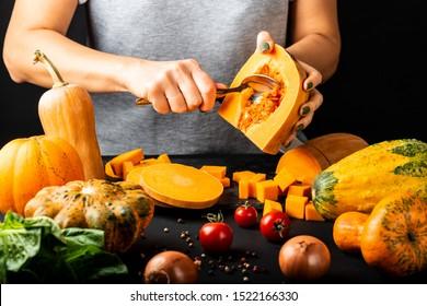 Woman peels and prepare pumpkin for cooking. Vegetarian healthy diet food concept.