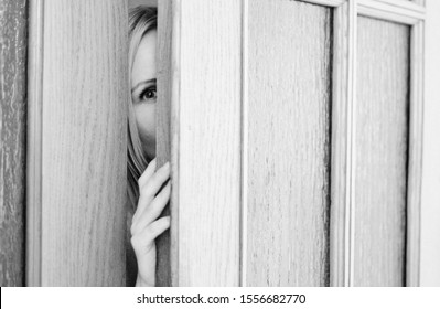 woman peeping through an open door