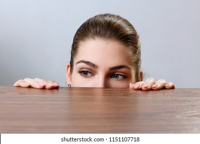Woman peeping under the edge of wooden table over gray background.