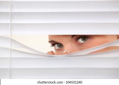 Woman peering through blinds