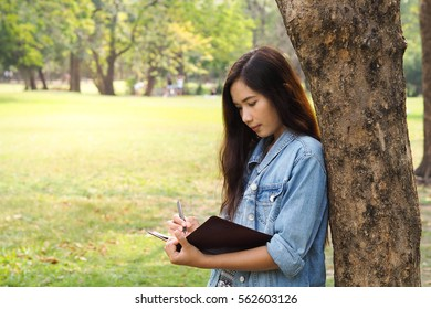 Woman with pen writing on notebook on grass outside