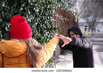 Woman with pepper spray defending herself against thief outdoors